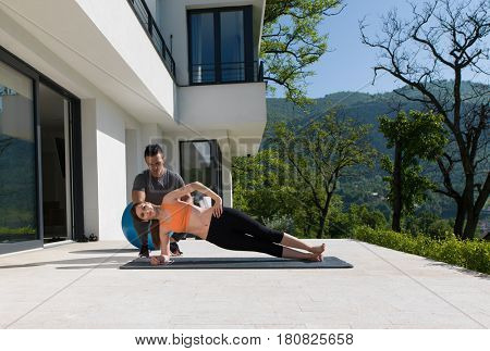 young handsome woman with personal trainer doing morning yoga exercises in front of her luxury home villa
