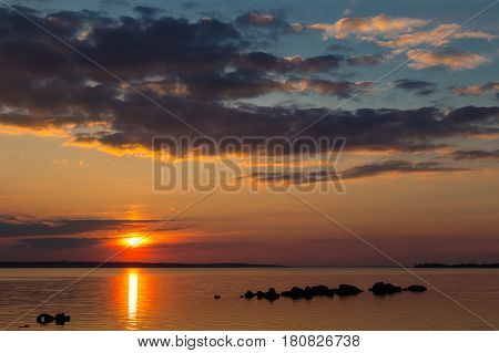 Fantastic red black sunset on the background of black sky. Sunny path on the water surface. Big sun on the horizon. Dark stones in the water. Reservoir. Dnipro. Ukraine night