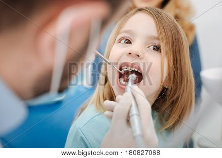 Just a little cleaning. Wonderful competent pediatric doctor fixing some issues with his little patients teeth while she paying him a regular visit and sitting with her mouth open