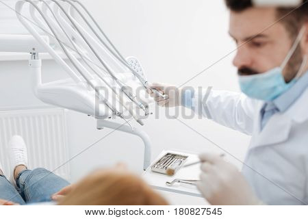 Just a little procedure. Thorough wise prominent specialist employing special dental instruments while treating his patients teeth and looking serious