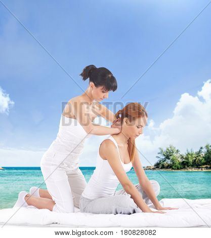Young woman getting traditional Thai stretching massage by therapist over marine landscape