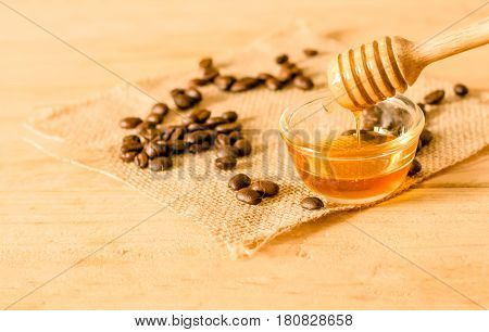 The Honey Dipper And Fragrant Honey Into A Transparent Bowl With Coffee Bean Isolated White Backgrou