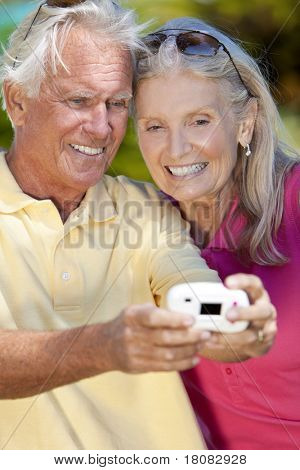 Happy senior man and woman couple taking a self portrait photograph with a digital camera together outside in sunshine