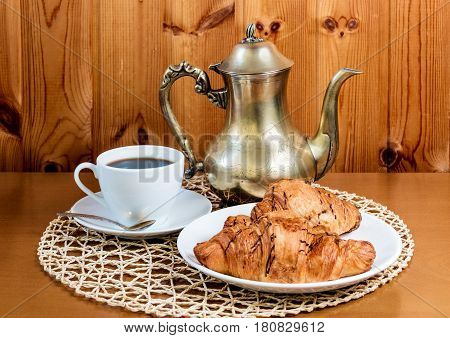 Cup of coffee croissants and coffee pot on table. Selective focus
