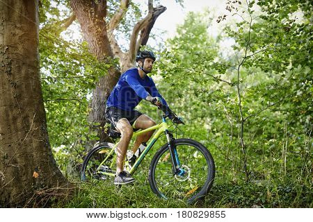 Man cycling on bike on trail in forest