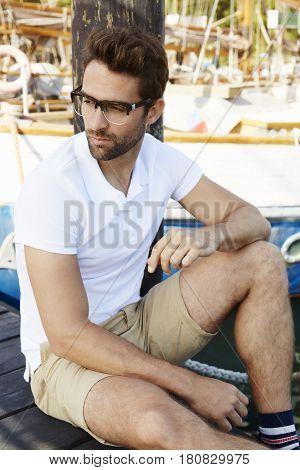 Handsome Dude sitting on dock looking away