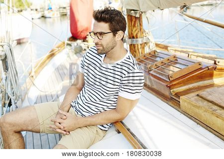 Handsome Guy sitting onboard boat looking away