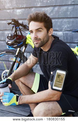Cyclist taking a break looking away having a drink