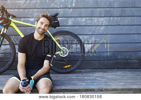 Happy relaxed Cyclist sitting and smiling at camera