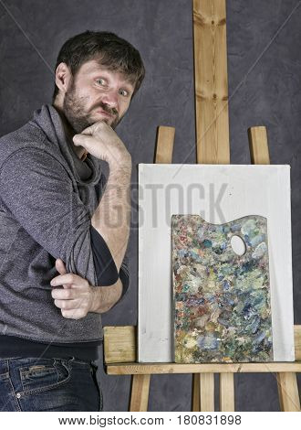 paint artist posing next to a canvas and contemplating, depicts a reverie. An empty easel, there is a palette on it