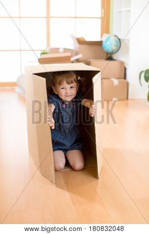 Happy child playing with boxes after moving in new house