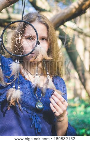 Witch Girl In A Fantasy Dress Is Looking Through A Dream Catcher With Beads And Feathers In A Forest