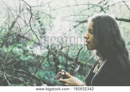 Witch Girl In A Fantasy Dress Is Smoking A Pipe In A Forest, Cold And Green Artistic Toning, Soft Se
