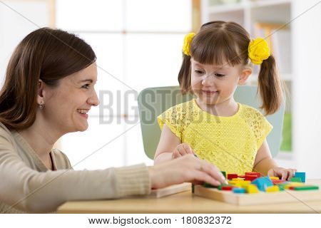 Woman and kid girl playing logical toys at home or daycare center