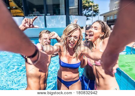 Multi-racial group of friends having fun in a swimming pool