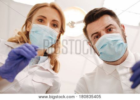 Would you show us your smile. Two great successful doctors working in team while wearing sterile uniforms and using special equipment