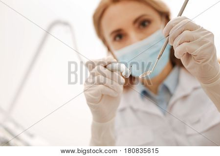 I will do no harm. Capable skillful busy dentist using professional equipment while treating caries and drilling a tooth