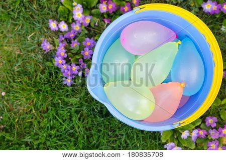 blue bucket filled with water balloons on a meadow