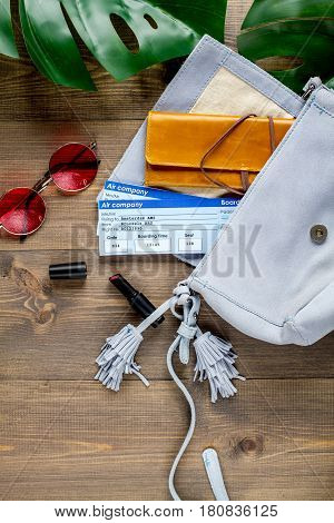 journey planning with tourist outfit and glasses, flight tickets on wooden table background top view