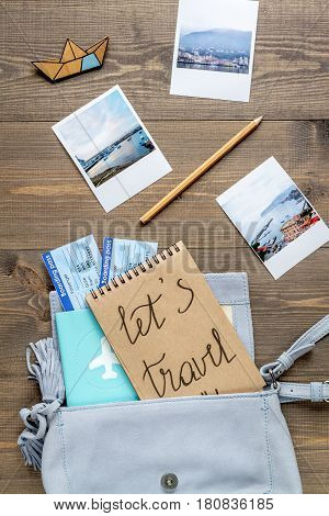 tourist stuff with passport, photos and flight tickets on wooden table background top view