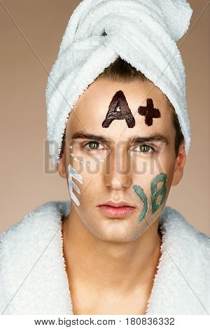 Vitamin E Vitamin A Vitamin B written on man's face. Photo of handsome man receiving spa treatments. Beauty & Skin care concept