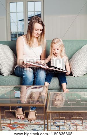 Mothers and Daughter at Home. Mum Reads a Book to her Daughter