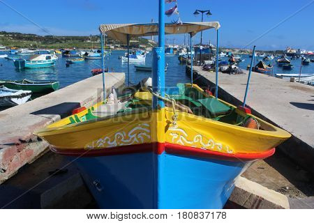 traditional colorful fishing boat in the harbor of Marsaxlok, a fisher village in the south of Malta