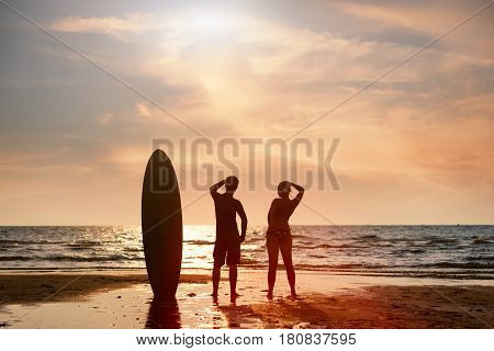 Surfer man and girlfriend standing happy on the beach looking out to the sea with the surfboards in the sunset after surfing.