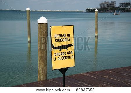 Beware od Crocodile yelow warning sign by the sea