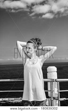 Young Athlete In Fitness Outfit Looking Aside At Embankment