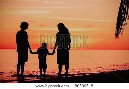 happy family with two kids on sunset tropical beach