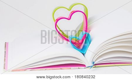 Red blue and green hearts over diary book on white table.