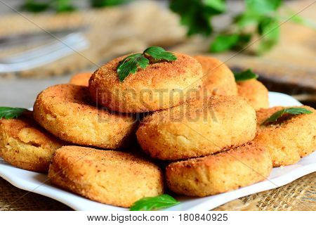 Crispy chickpea fritters on a plate. Fried veggie fritters made with chickpeas puree. Meatless dish idea. Rustic stile. Closeup