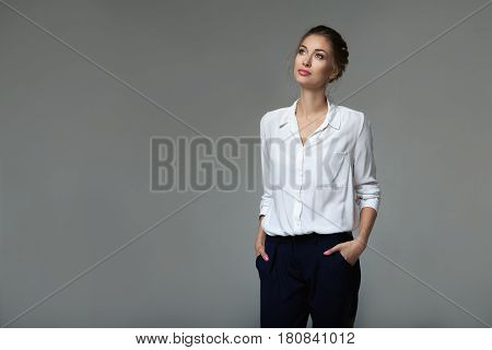 Beautiful young buisness woman in studio. Gray background