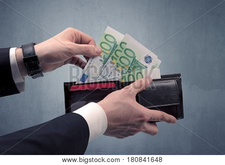 Businessman's hand in suit takes out eruo from his wallet