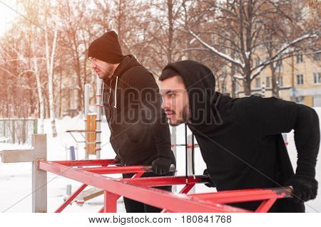 Winter fitness. Two muscular men doing workout on parallel bars.