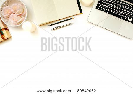 Stylish feminine work place. White office desk table with laptop, roses, vintage white tray, notebook, coffee cup, pen and pencil. Top view with copy space, flat lay poster