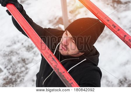 Winter fitness activity. Male adult in black sportswear exercising on parallel bars outdoors.