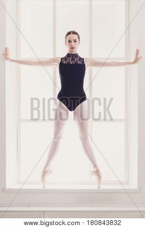 Classical Ballet, ballerina portrait. Beautiful graceful dancer in black practice releve ballet position near large window in light hall. Ballet class training, high-key soft toning. Vertical image