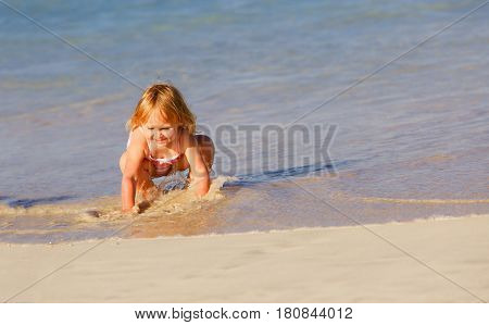 happy little girl play with water at tropical beach