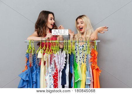 Brunette young woman showing at nameplate sale to her friend blonde young woman standing near hangers