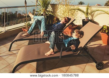 Dad and little son relax on balcony terrace