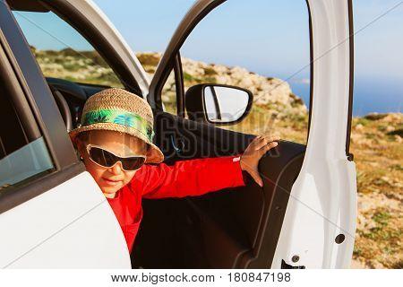 happy cute little boy travel by car in mountains