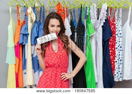 Portrait of young beautiful woman nameplate 'sale' in hands near hanger