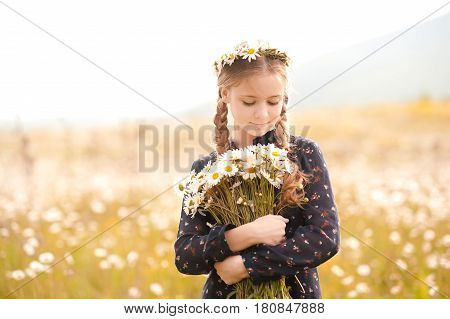 Smiling teen girl 14-16 year old holding flowers standing in meadow. Springtime.
