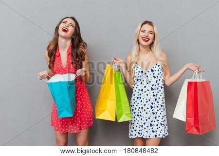 Beautiful woman whining about her one package while her blonde friend woman holding four packages isolated over grey background