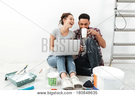 Picture of laughing young loving couple sitting on floor in new flat makes repair and using laptop computer drinking tea. Looking aside.