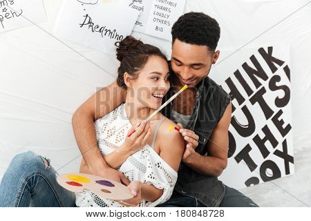 Picture of cheerful young loving couple artists sitting on floor over white background. Looking aside.