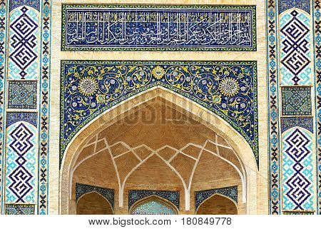 Old-time central asian styled wall of pishtak with pointed arche and persian paintings