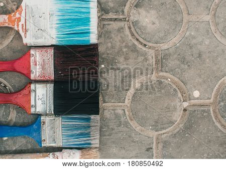 Multicolored brushes on a stone floor. Top view